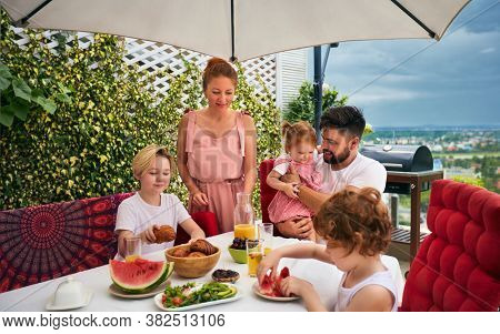 Happy Family Having Lunch On Rooftop Patio At Home