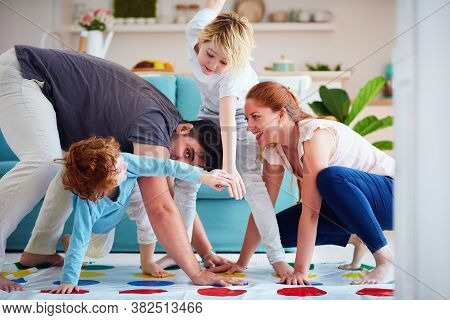 Cheerful Family Having Fun, Playing Twister Game At Home
