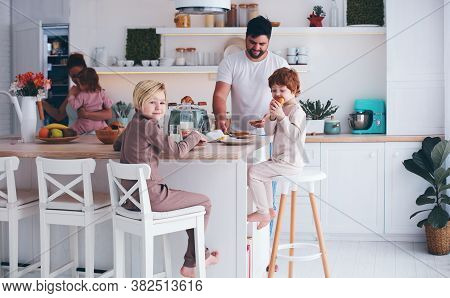Happy Family With Three Kids Having Breakfast At Home In The Morning, Cute Kitchen Interior
