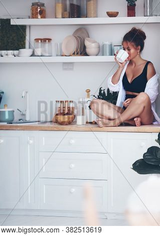 Pretty Woman Drinking Coffee Sitting On Kitchen Countertop In The Morning