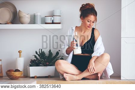 Pretty Woman With Bottle Of Milk Sitting On Kitchen Countertop In The Morning