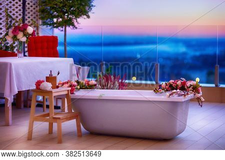 Taking Bath In Bathtub With Flowers At Rooftop Patio At Warm Summer Night