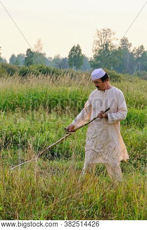 An Senior Asian Man In An Embroidered Skullcap And White Traditional Clothes Mows Hand-scythe Grass