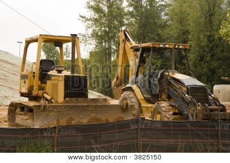 Two pieces of heavy construction equipment moving dirt behind a plastic silt fence poster