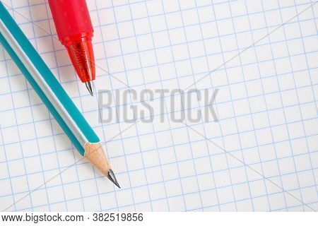 Light Background On A School Theme With Place For Text. Wooden Pencil And Red Pen Lie On A Squared N