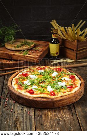 Italian Pizza With Tomatoes Mozzarella Cheese And Arugula On The Wooden Table