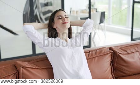 Dreamy And Calm Young Female Sitting On Couch Wearing In Casual Wear, Holding Hands Above Head, Clos