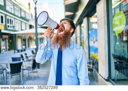 Young redhead businessman with angry expression. Screaming using megaphone at street of city.