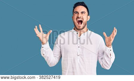 Young handsome man wearing casual clothes crazy and mad shouting and yelling with aggressive expression and arms raised. frustration concept.