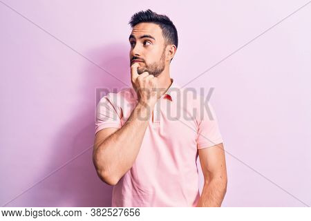 Young handsome man with beard wearing casual polo standing over pink background thinking concentrated about doubt with finger on chin and looking up wondering