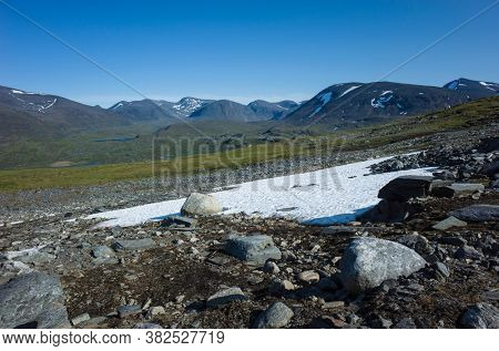 Swedish Lapland landscape with snow and fragile vegetation. Arctic environment of Scandinavia in summer sunny day with blue sky. Nordkalottruta Arctic hiking Trail in northern Sweden