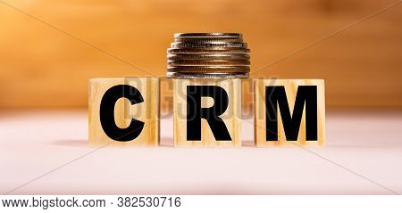 The Concept Of The Word Crm On Wooden Cubes With Coins On A White Wooden Background. Business Concep