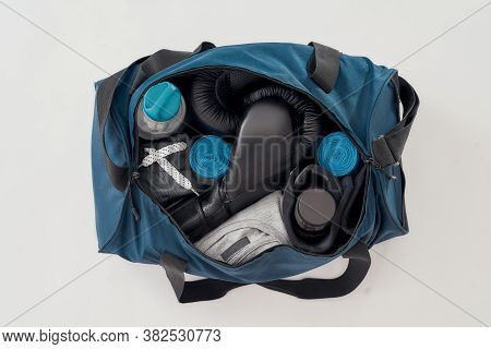 Best Training Equipment. Top View Of A Sports Bag With Boxing Gloves, Hand Wraps, Sport Clothes, Bot