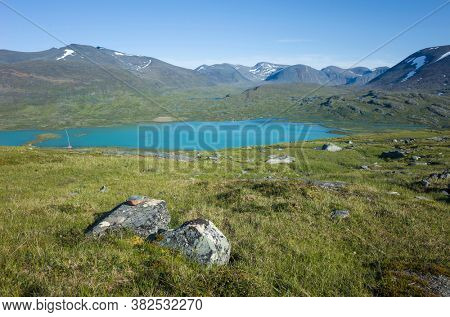 Swedish Lapland landscape. Arctic environment of Scandinavia in warm summer sunny day with blue sky. Lake Alisjavri on Kungsleden and Nordkalottruta Arctic hiking Trail in northern Sweden