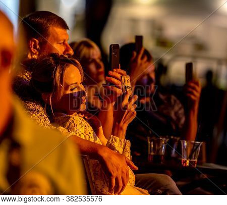 Odessa, Ukraine - Cirka 2020: Spectators At Concert In Theater Take Pictures Of Performance Of Their