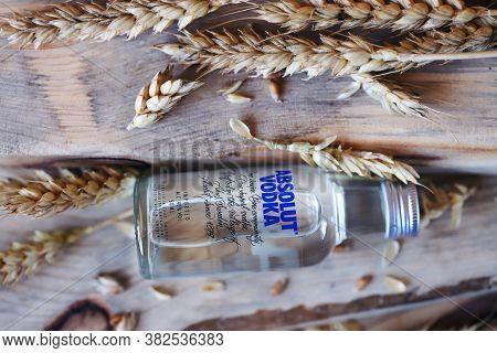 Kharkiv / Ukraine - 08 23 2020: Bottle Of Absolut Vodka 50 Ml On A Wooden Background. Wheat Ears, Wh