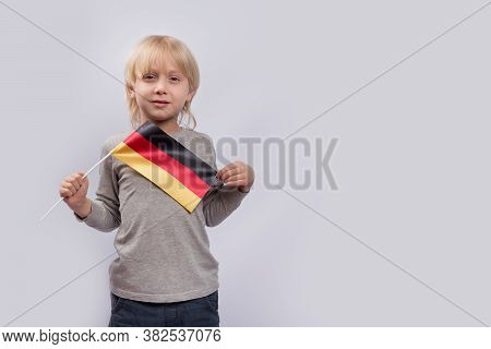 Serious Fair-haired Boy Holding The Flag Of Germany. Immigration To Germany