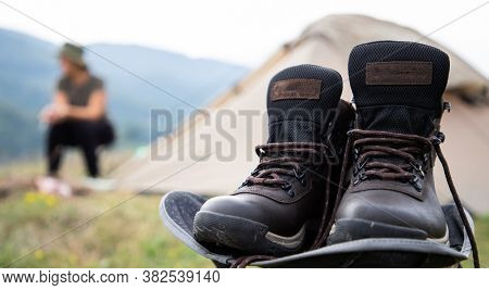 camping in mountains background focus on trekking boots