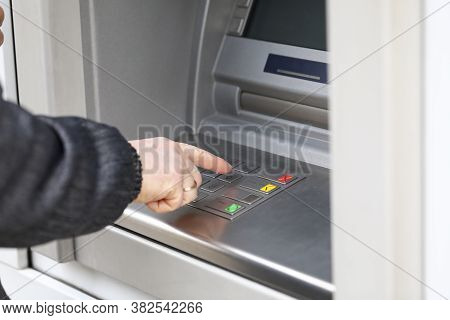 Man Dials Pin Code To Withdraw Money From Atm. Man Stands Nea Terminal To Withdraw Money. Payment Fo