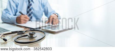 Focus On Stethoscope, Banner And Copy Space. Senior Doctor Male Sitting Working At The Desk In Medic