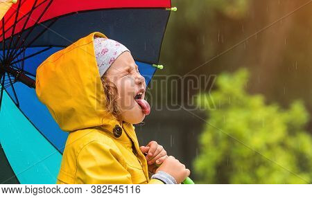 Funny Little Girl In Yellow Waterproof Coat. Kid Face With Open Mouth Catching Drops. Child With Col