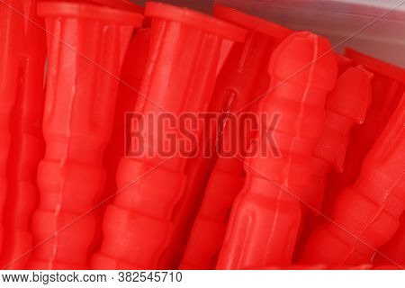 Red Plastic Dowels For Self-tapping Screws Close-up.