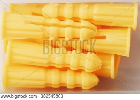 Yellow Plastic Dowels For Self-tapping Screws Close-up.