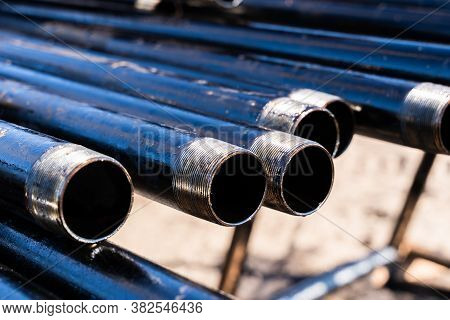 Pipe For Drilling Rigs For Oil And Gas On Background. Drilling Of Oil And Gas Wells. Drill Pipe. Tub