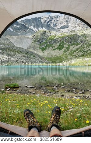 Pov Selfie Shot Of Mans Feet In Trekking Boots Against Majestic Landscape Of Mountains And Lake. Ext
