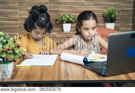 Two Kids Busy In Writing By Looking Into The Laptop During Online Or Virtual Class At Home - Concept