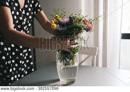 Young Caucasian Woman With Black Dress And White Polka Dots Arranging A Bouquet Of Freshly Picked Up
