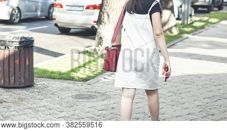 Beautiful Girl With A Red Bag Walks In The City