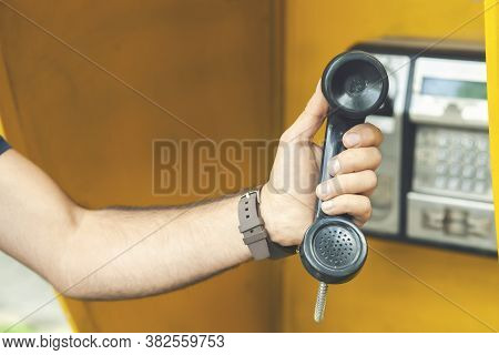Young Man Picks Up The City Payphone
