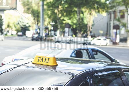 Black Taxi Cars With Yellow Standard Signs On Top Parked Or Stoped On Busy City Street, Taxi Service