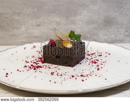 Brownie Served On A Plate. Brownie Is Decorated With Almond In Caramel, Mint And Raspberries.