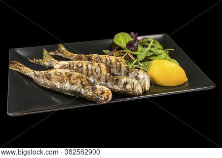 Delicious Whole Fried  Bluefish With Lemon On A Plate With Reflection, Isolated On Black Background