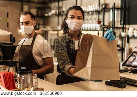 Coffee shop owners with face masks, lockdown, quarantine, coronavirus, back to normal concept, packing takeaway order