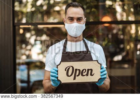Man coffee shop owner with face mask opens after lockdown quarantine