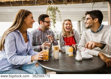 Group Of Four Friends Having Fun A Coffee Together. Two Women And Two Men At Cafe Talking Laughing A
