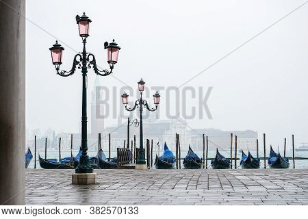 Romantic Promenade In Venice With Street Lamps And Blue Gondolas Docked In The Grand Canal, During A