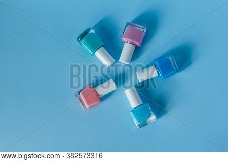 Multi-colored Nail Polish Lie On A Blue Background Forming A Circle. Nail Care Salon. Manicure And P