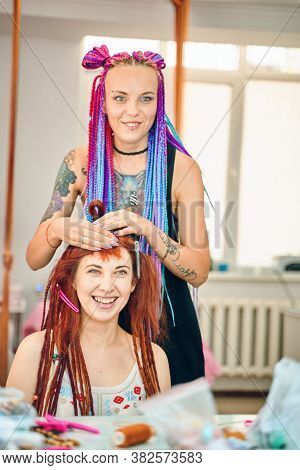 Barber Braids Dreadlocks. Process Of Braiding The Master Weaves Braids On Her Head In A Beauty Salon