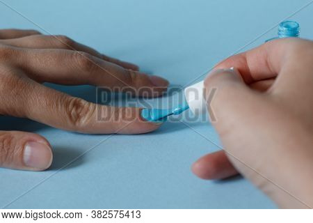 Woman At A Nail Care Procedure. A Manicurist Paints A Girl's Nails On Her Hand With Blue Nail Polish
