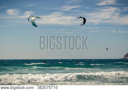 Guincho Beach Sea With Surfers Doing Kitesurf And With The Blue Sky In The Background, Cascais, Port