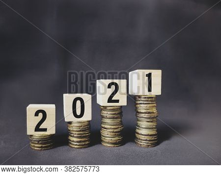 2021 Number Written On Wooden Blocks On Top Of Coins Stacks Background. Business Concept. Stock Phot