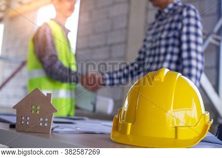 Contractor And Engineer Shaking Hands To Agree To Build A House Or Building. The Construction Worker