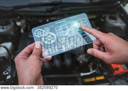 Car Engine Diagnostic Concept. Car Mechanic Holding In Hands A Digital Frameless Computer With Chart