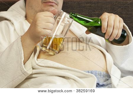 Man sitting on the couch with a beer in the hands of