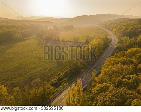 Aerial View Flying Over Road With Car Moving, That Through Lane Green Forest. Car Driving Along The