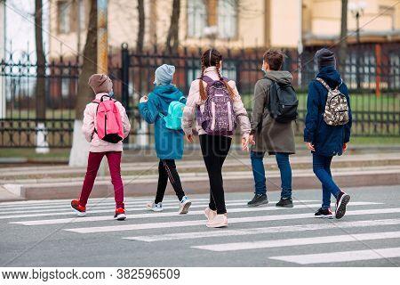 School Children Cross The Road In Medical Masks. Children Go To School.